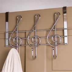 """Great for your backstage dressing room door, or just as useful on your closet door. Our substantial steel door hanger will show your love of music while keeping your outfits off the floor. Three ball-tipped hooks. Measures 12 1/4"""" x 10"""". Hangs over any 1 1/2"""" thick door."""