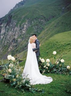 Organic outdoor wedding with with wild flower ceremony backdrop.