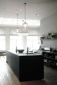 Those clear glass pendants, that circular chandelier.  What a lovely black matte kitchen with those wide plank wood floors, open shelves with that pale pottery.  Swoon.