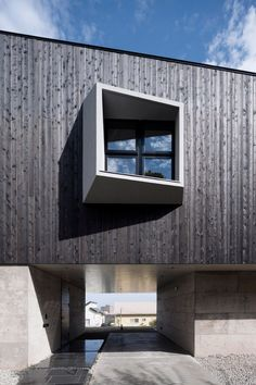 An angular, blackened wood structure sits atop two concrete blocks to form this house in Japan's Kanagawa Prefecture, designed by Cubo Design Architect.