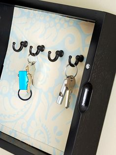 Turn a shadowbox into a key case. For a decorative touch, line the back of the box with scrapbooking paper that complements your decor. Screw in a row or two of hooks, depending on your needs. If keys are not distinctive, include a small label above each hook for easy identification. Hang the box on the wall next to the front door.