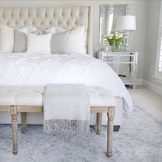 Bedroom inspo,  tufted linen bed, mirrored nightstand, white bedding, tufted linen bench, gray Safavieh rug, Benjamin Moore classic gray paint in walls, chantilly lace paint on trim , target gray blanket, white tulips, white Pom Pom pillow and duvet,   (@thedecordiet) on Instagram: