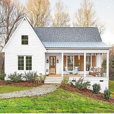 The perfect white house -- love the natural wood accents. Modern farmhouse, metal roof, front porch living.