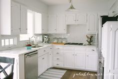 A gorgeous traditional white kitchen with white subway tile, stainless appliances & rustic wood floors
