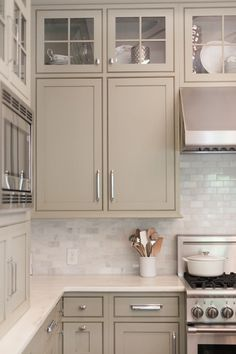 Light gray cabinets + pearly white backsplash makes the kitchen sophisticated
