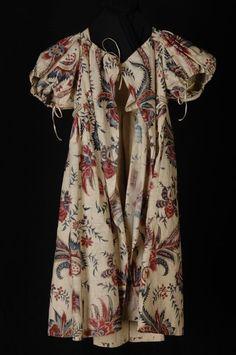 1810 EMPIRE KINDERJURK OF JAK VAN KATOENEN SITS, WIT FOND MET GROTE VEELKLEURIGE BLOEMEN, ROOD, BLAUW EN PAARS, POFMOUWEN, RUITVORMIG OPENVALLEND RUGPAND