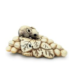An Ivory Netsuke Edo Period (18th century) Of a squirrel on a bunch of grapes, eyes inlaid in cowhorn, Kyoto School 5.8cm. long