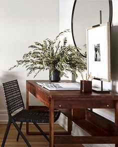 Small but lovely workspace with wooden desk and round hanging mirror | Dan Mazzarini