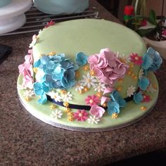 Bottom tier: Madeira cake with vanilla buttercream and mix of flowers on soft green fondant