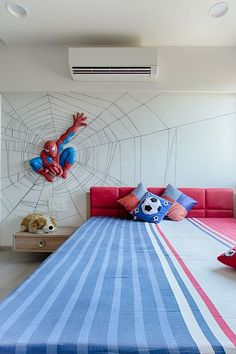 View of bed room with wooden bed having very comfortable back rest having upholstery work. Back wall with wall mural design .The mural created with spider web having spider man mural .