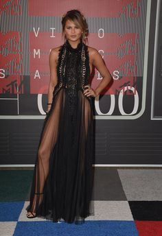 "Chrissy Teigen's VMAs dress may feature a high, ruffled neck, but that's where the ""modest"" details end. Her long, black Marchesa gown was entirely sheer, was embellished with shimmering stones, and showed lots of side boob. Chrissy also showed"