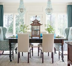 Turquoise + white dining room with wing back chairs, twin bead chandeliers