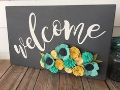 Let this sign give your guests a bright welcome to your home. This sample is painted with a dark gray chalk paint and then topped with some fun-loving felt flowers. (YES - you can request custom colors!) All signs are individually made, and the flowers may not be exactly as shown here. This keeps each sign unique! Sign measures approximately 11-1/2 x 18  Please allow 1-2 weeks for your sign to be created and shipped.