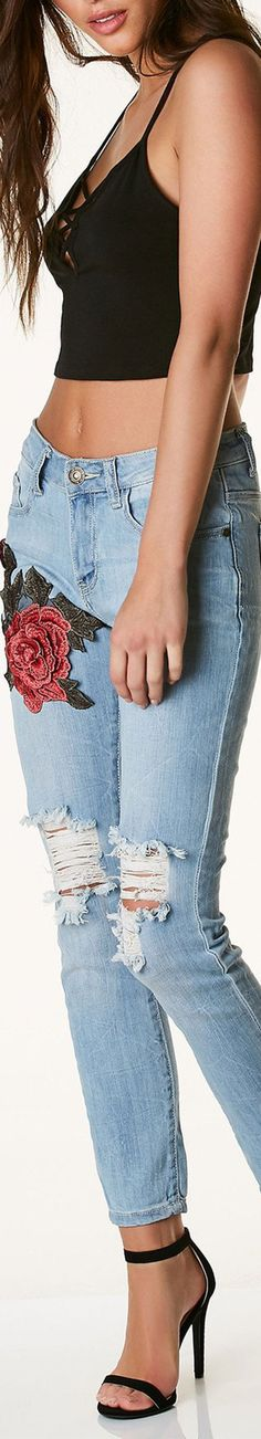 Light washed mid rise jeans with distressing in front and floral patch on one side. Five pocket design with button and zip closure. - Cotton-Spandex blend - Imported - Model is wearing size 3 - Runs t