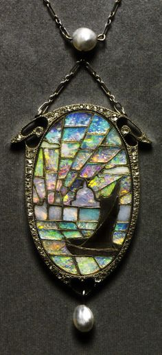 An Art Nouveau opal pendant, by Archibald Knox, circa 1900. Composed of platinum, gold, enamel, diamond and opal. In this pendant for Liberty & Co., Knox used opal mosaic to depict a painterly scene of a boat outlined by a fiery sunset on London's River Thames. Source: Artistic Luxury - Fabergé Tiffany Lalique