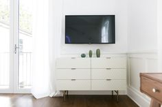This modern white dresser is being used for makeup storage, which is much cuter than a bunch of containers!