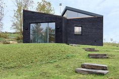 Dutchess County Studio is composed of three rectangular volumes arranged in a pinwheel to overlap one another. Textured black brickwork walls are slanted at the top to meet with triangular clerestory windows. Three Bedroom House, Black Brick, Clerestory Windows, Brick Architecture, Tiny House Cabin, Tiny Houses, Huge Windows, Garden Studio, Black Exterior