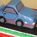 A Car Theme Cake driving down a road.
