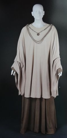 The costume was a cloak made with soft natural fabrics and had billowing, oversized kimono sleeves with a muslin lining. A dark jersey gown was worn under the cloak, which exposed the jersey's sleeves...the costume did receive a necklace that hung low from the shoulders. The pendant was a greeblie