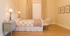 """Leveza e aconchego, típicos das casas provençais, marcam o dormitório de casal (35 m²). O teto inclinado revestido por lambris brancos e com madeiramento aparente e o piso de canela de demolição (Ouro Velho) acentuam o ar """"cottage"""" (casa de campo). O tecido floral (Celina Dias) na roupa de cama, no revestimento do banco e nos quadros da parede dão o toque campestre"""
