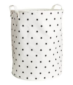 White/stars. Cylindrical storage basket in thick polyester with a printed motif and two handles. Concealed metal rim at top for stability. Plastic coating