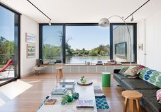 modern lakeside home in Australia living room with arco lamp by flos, b&b italia coffee table, and poltroon frau sofa