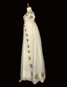 A RARE IVORY SILK CREPE DRESS, CIRCA 1810  the fine, transparent gauze embroidered with bands of deep pink roses, seen here worn over