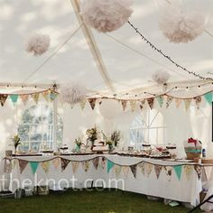 long rows of tables and covered them with white linens, burlap runners, and vintage fabric placemats. Fabric flags and tissue poofs hung from the tent ceiling.