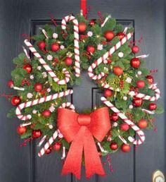 une couronne de Noël DIY de branches de pin décorée de bâtons de sucrerie et un ruban rouge