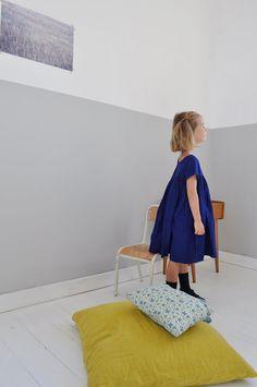 White & grey wall, blue dress, ochre pillow...great palette.