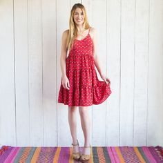 This Red Flora Adrienne Dress features thin straps, a hem that hits just above the knee, and low, v-shaped back. The tiered and flowy skirt makes this perfect for Spring and Summer! •100% Cotton. •Fit Detail: Tighter fit around bust line with flowier fit through the skirt.