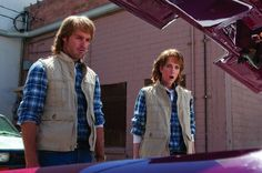 """MacGruber and Vicki From MacGruber: For him: The MacGruber uniform is a plaid shirt, khaki vest, aviators, and jeans, and of course, a mullet wig.  For her: Though Vicki could also be copied by wearing a feathered wig and a '70s getup, I much prefer the scene of her from the movie where she has to play MacGruber's decoy and has to dress exactly like him. See the """"He wears"""" description for the outfit."""