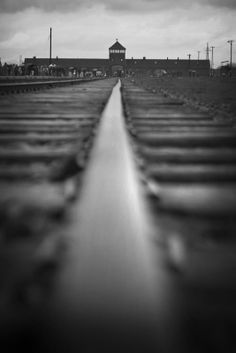 Rails of the unloading ramp at the Auschwitz II-Birkenau camp with the main camp gate in the distance.
