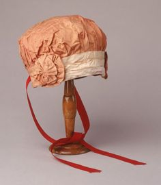 1910 Bathing cap; Bathing cap of orange cotton sateen, backed with a rubber solution to make it waterproof. Shallow crown gathered into band around forehead, decorated at centre front with three horizontal pleats of cream silk, and at each side with a cotton sateen rosette.