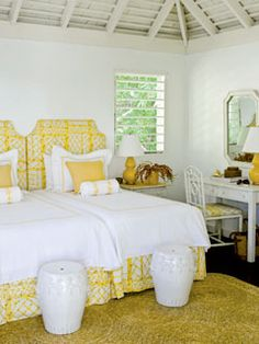 Another guestroom with symmetrical twin beds pushed together, this time with garden stools to punctuate the end of the beds. #guestrooms #gardenstools #yellowandwhite
