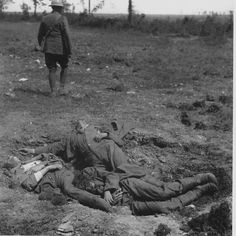 WW1: Germans, one of them a soldier (?), are left where they fell after execution by firing squad. Possibly spies. An English soldier walks away from the scene; undated.