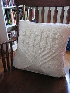 Hanukkah is the Jewish Festival of Lights, and it's most recognizable symbol is the menorah--the nine branched candelabra on which candles are lit and blessed, one by one, over the eight days of celebration. Contemporary menorahs are made from all kinds of materials - the elegant one on the front of this pillow is crafted from knitted cables in a luxurious blend of wool and cashmere, inviting rest for a holiday weary head.