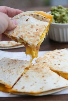 A hand holding one slice of a Breakfast Quesadillas with bacon, egg and cheese.