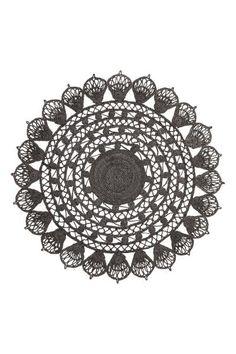 Tapijt met opengewerkt dessin: Een rond tapijt van jute met een opengewerkt dessin.