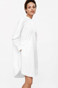 Made from crisp cotton, this shirt dress has a fitted waist with a kimono sleeved cape effect top. it is completed with a neat collar, a slightly graduated hemline and hidden front buttons.