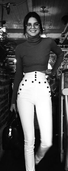 Who made Kendall Jenner's white button pants, tan turtleneck sweater, and black leather handbag?