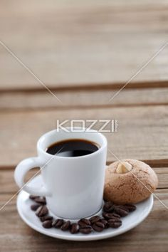 coffee cup with beans and cookie. - Close-up shot of coffee cup and saucer with coffee beans and cookie on wooden plank.