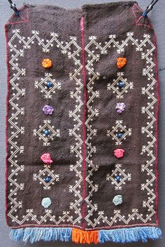 A traditional woollen 'önlük' (apron) from the Domaniç area (the northernmost district of the Kütahya province). For women.  Ethnic group: Yörük, 1925-1950.  Adorned with embroidery in white cotton, six blue glass beads and multicoloured pom-poms (with a metallic sequin in their center); the lower border is edged with woollen fringes.  (Inv.nr. önL040 - Kavak Costume Collection - Antwerpen/Belgium).