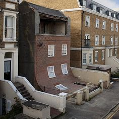 "British designer Alex Chinneck created an art installation - "" From the Knees of my Nose to the Belly of my Toes "" by removing the facade of a derelict 4-storey house & replacing it with a brand new frontage that leaves the crumbling top storey exposed, then curves outwards so the bottom section lies flat in front of the house."