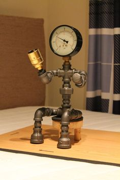 Items similar to Sitting Pipe lamp made from malleable steel pipe fittings making use of a pressure gauge as the head. sat on a simple wooden bench. on Etsy Pipe Bookshelf, Gas Pipe, Pipe And Drape, Industrial Pipe, Wooden Lamp, Pipe Lamp, Pipe Furniture, Unique Lighting, Lamp Design