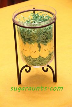 Place a drinking glass in the center of a vase and fill the outer rim with filler grass/peeps/jelly beans...Water and flowers go in the center glass. By the Sugar Aunts.