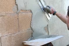 """I'm looking to """"stucco"""" the wall with a cement/stand mixture... technically it's parging, not stuccoing Diy Stucco Exterior, Stucco Repair, Stucco Homes, Wall Exterior, Bungalow Exterior, Cottage Exterior, Exterior Colors, Concrete Block Walls, Cinder Block Walls"""