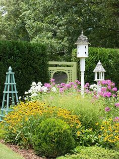Even a small garden can become a haven for birds and butterflies when you choose flowers they prefer. For example, this square bed is packed with bird and butterfly favorites, such as black-eyed Susan and phlox. A bird feeder and birdhouse add to the garden's wildlife-friendly features./