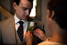 mother of the groom pinning his boutonniere