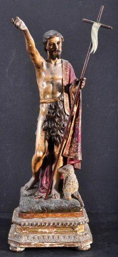 Imagem em madeira esculpida, entalhada, pintada e dourada representando São João Batista. Tendo aos pés uma ovelha. Olhos de vidro. Peanha dourada de feição Neo- clássica. Altura 38 cm. Altura com penha 44 cm. Portugal século XIX. Base R$1.000,00